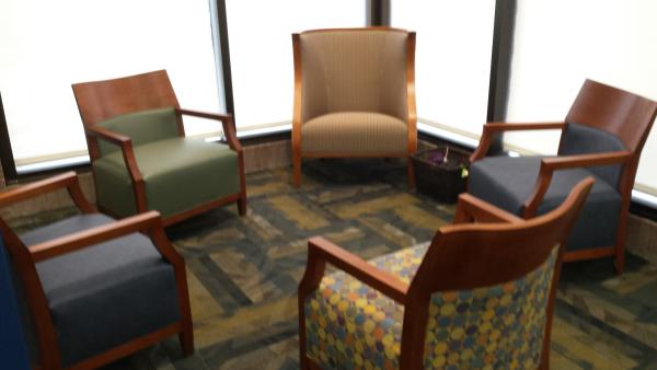 Array of comfy chairs in a circle with a basket of knitting materials nearby