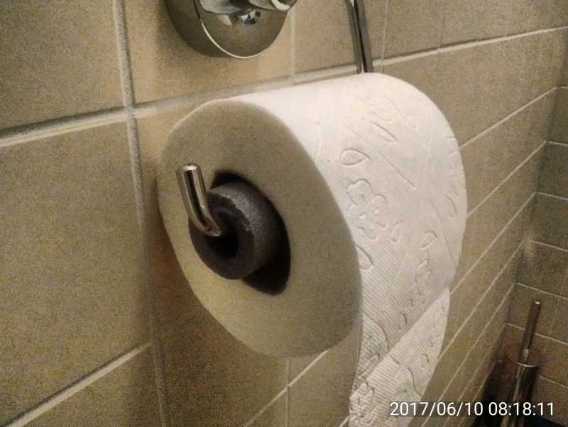 Toilet roll holder with roll in place
